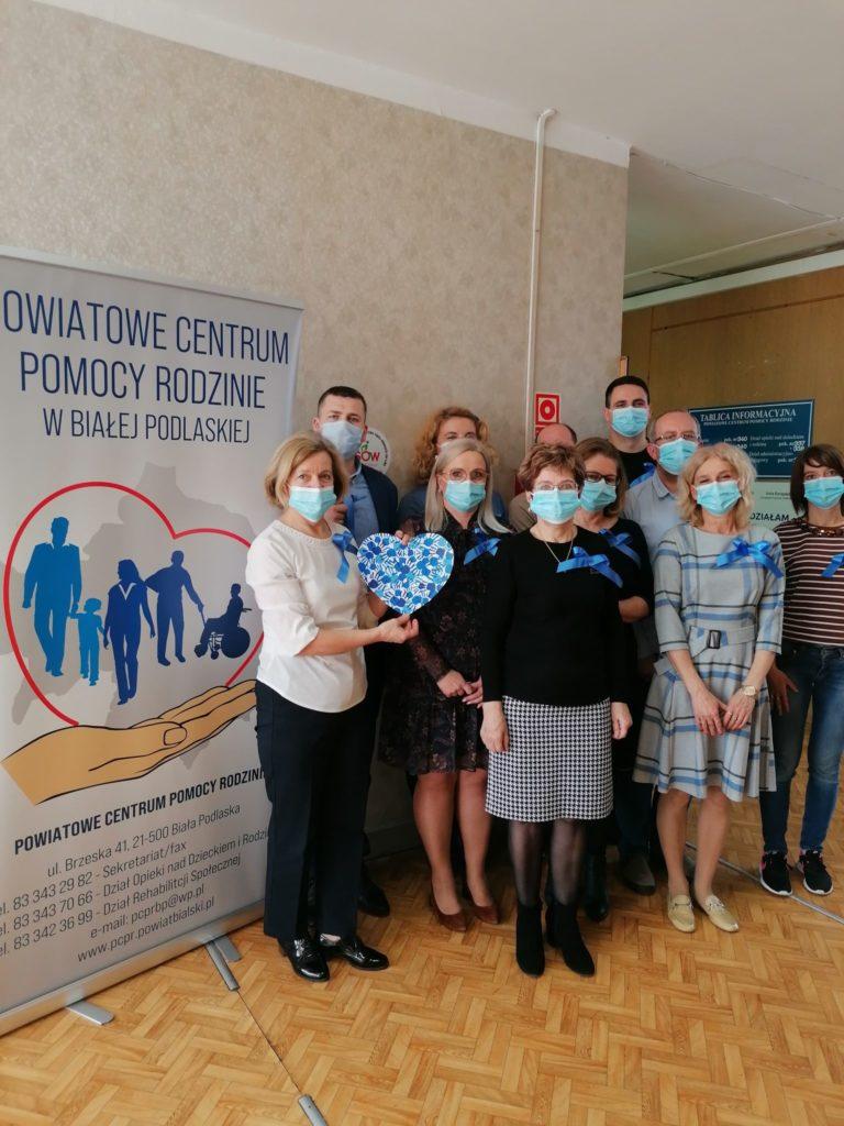 Zdjęcie grupowe przedstawiające pracowników PCPR z przypietymi niebieskimi kokardami z okazji obchodów Światowego Dnia Świadomości Autyzmu